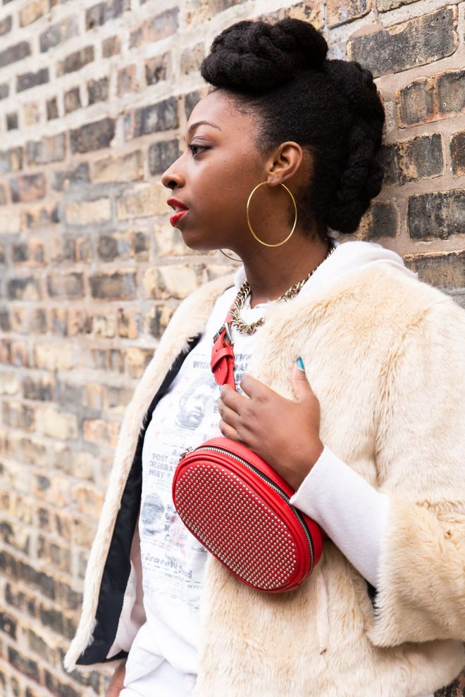 girl looking to the side-wearing red fanny pack on chest-a faux fur jacket and hoodie-the haute seeker