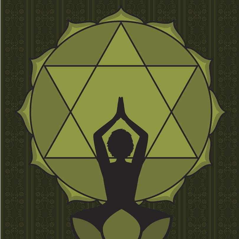 woman practicing yoga in front of heart chakra symbol