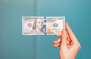 woman's hand holding 100 dollar bill