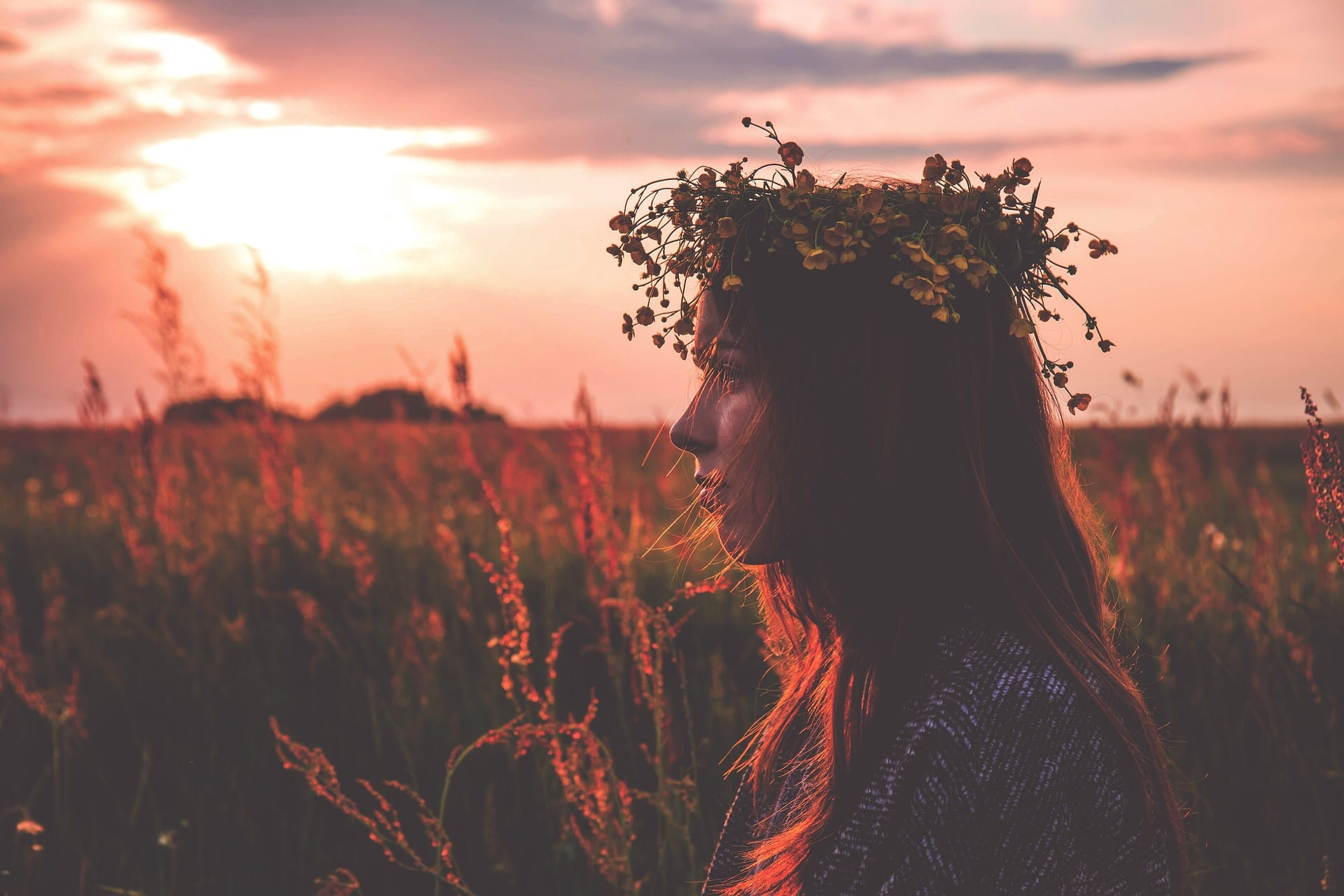 woman in flower crown in a field at night
