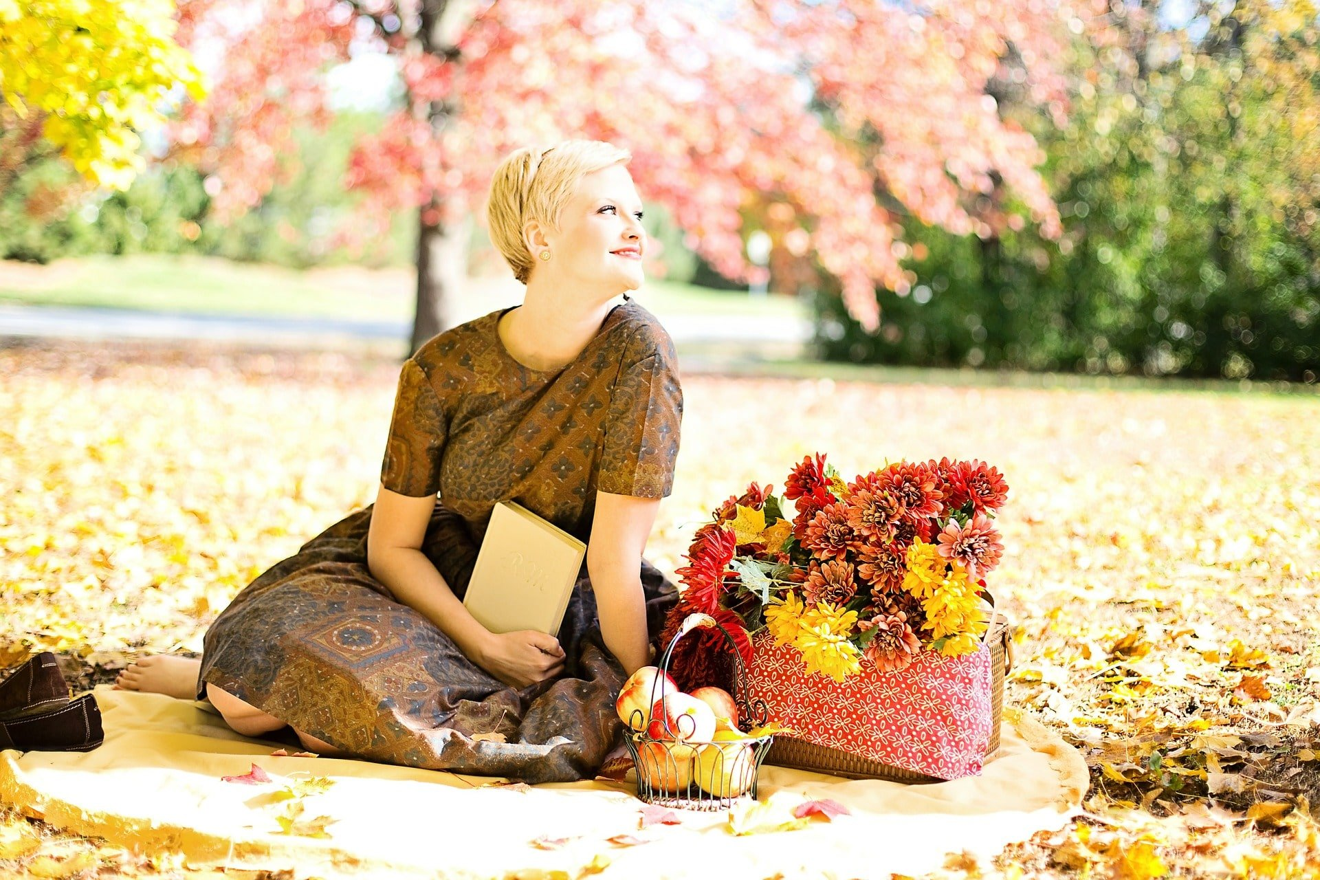 woman sitting outside reading quotes next to a basket of flowers