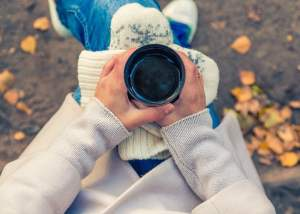 woman sitting outside holding a cup of coffee