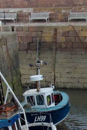 The gauge is on the harbour wall behind the boat