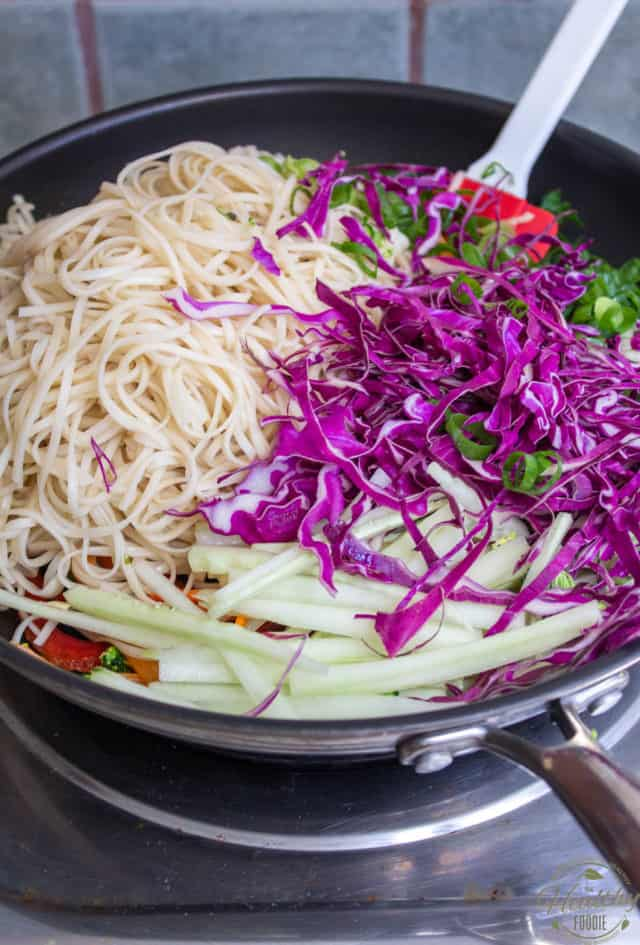 Add the drained noodles, cabbage, cucumber and green onions to the pan