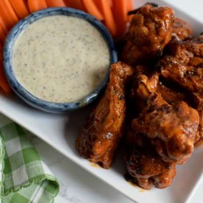 A close up picture of buffalo wings on a white platter with ranch, carrots, and celery.