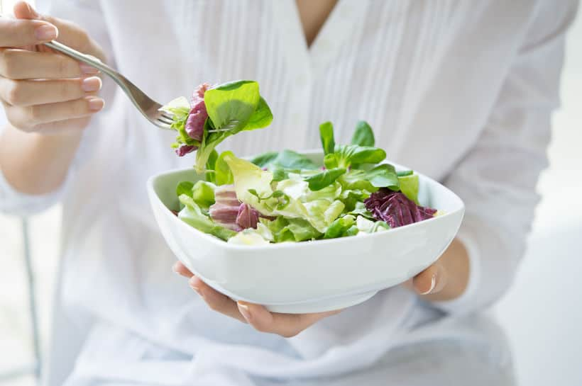 A woman in a white shirt eating a salad.
