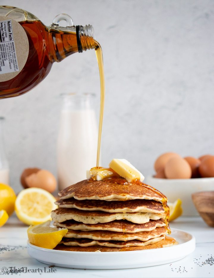 Stack of lemon pancakes with maple syrup drip and pads of butter.