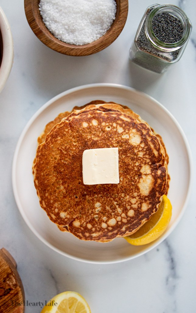 Over head shot of pancakes with butter and lemon wedge.