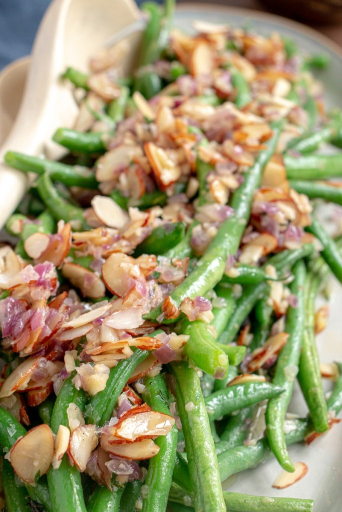 up close of green bean almondine with sauce spooned over top