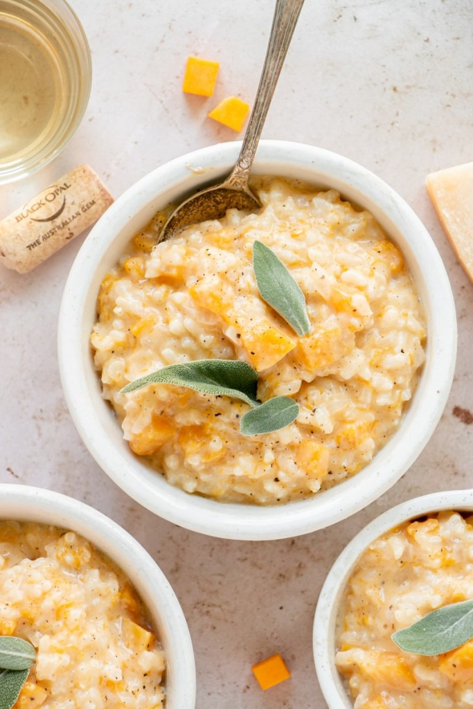 bowl of butternut squash risotto with fresh sage and a glass of wine