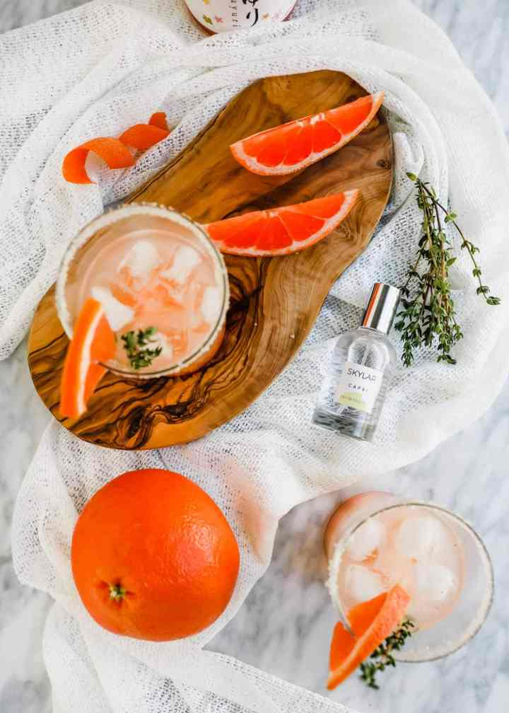 Grapefruit Honey Sake Cocktail in glasses with grapefruit and Skylar perfume flatlay.