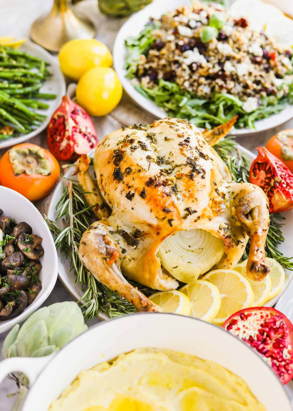 Whole roast chicken on plate stuffed with onion with lemons, artichokes, persimmons, pomegranates, and side dishes in background.