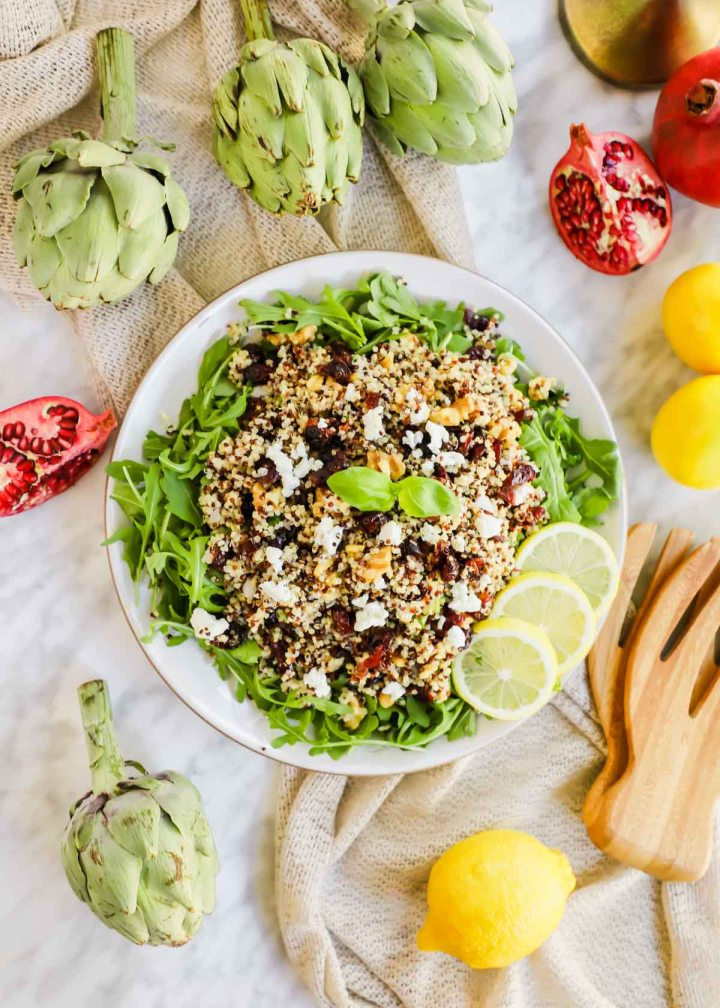 Harvest Salad with Quinoa and Arugula and lemon slices on plate flatlay.