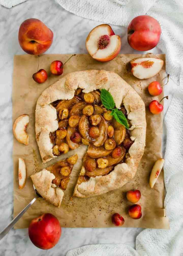 White Peach and Cherry Galette on parchment paper with sliced peaches and cherries flatlay.