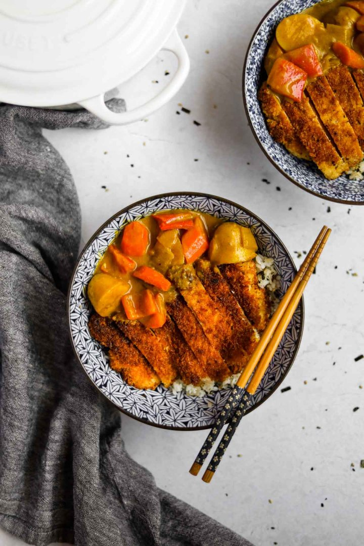 Overhead shot of Chicken Katsu Curry in a blue Japanese porcelain bowl with blue and wood bamboo chopsticks and a white Le Creuset dutch oven