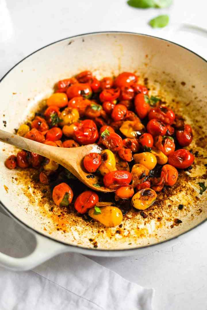 Blistered Cherry Tomatoes with olive wood spoon and Le Creuset White Braiser.