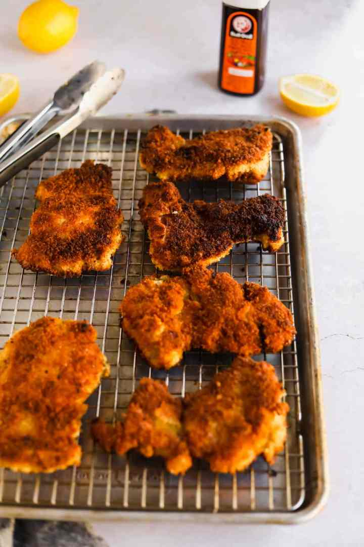 Fried chicken katsu on cooling rack and baking sheet with lemons, tongs, and bulldog tonkatsu sauce.