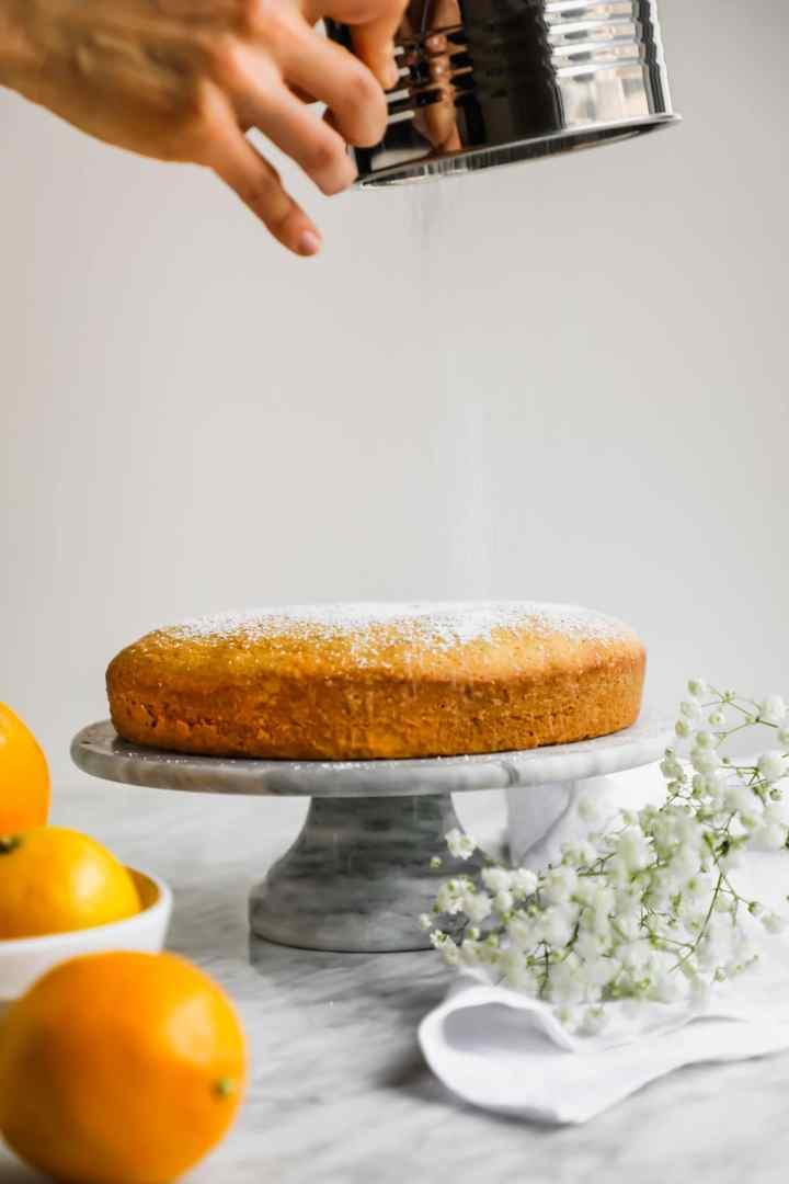 Sprinkling powdered sugar on Meyer Lemon Olive Oil Cake