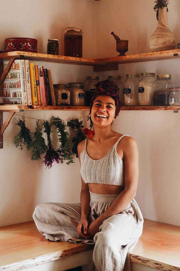 Cat Seixas sitting in her kitchen with herbs hanging behind her