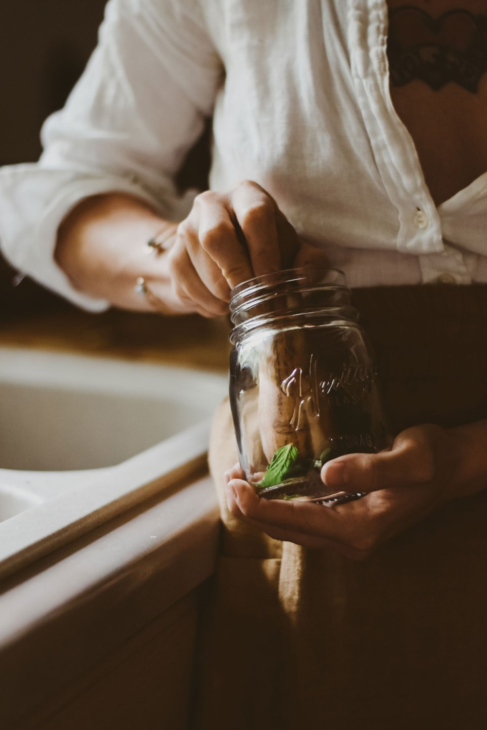 A woman putting herbs into a glass jar in kitchen