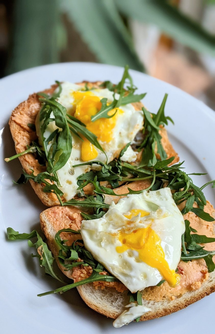 open faced cheese egg and arugula sandwich with pub cheese spread port wine or white cheddar spreadable cheese on brioche toast with leafy greens and a fried egg on top vegetarian fancy breakfasts bougie as hell great hungover breakfast ideas without meat