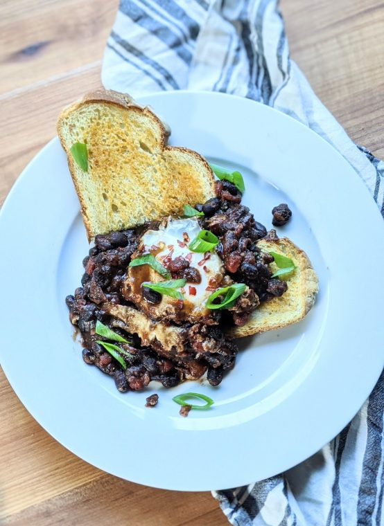 shakshuka with black beans on garlic toast with green onions tomatoes salsa verde eggs and beans breakfast and brunch recipes without gluten and meatless brunches mexican flavors