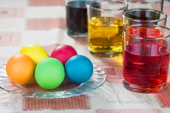 Plate with brightly colored Easter Eggs and glasses with beautiful dyes