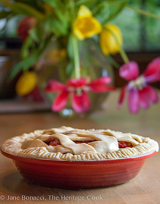 Strawberry-Rhubarb pie in red pie plate in front of bright tulips