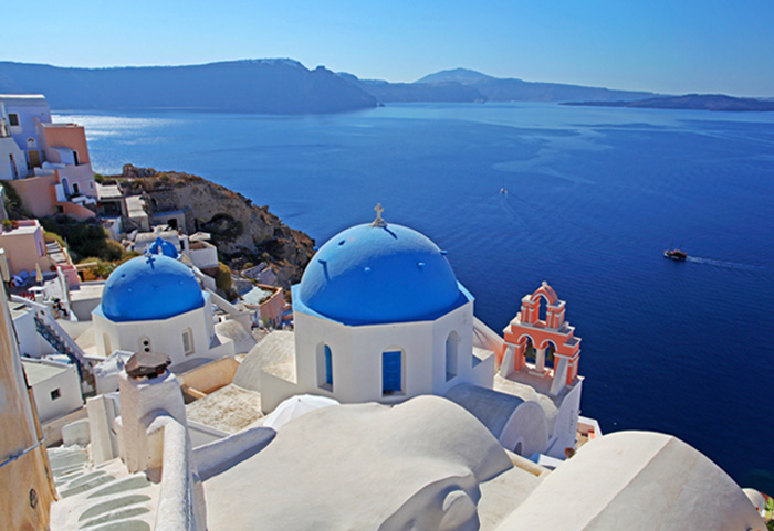 Photo of Santorini, Greece with white buildings and the deepest blue ocean