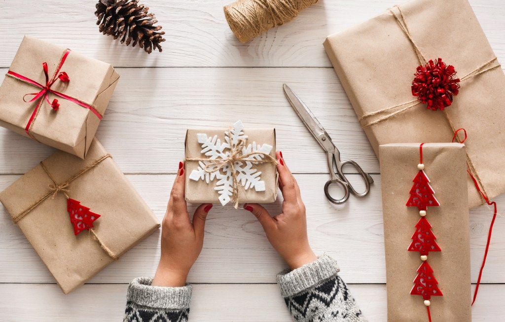Top down view of a woman's hands as she decorates gift boxes for Christmas and the holidays; 2017 Holiday Gift List for Cook from The Heritage Cook; Jane Bonacci, The Heritage Cook