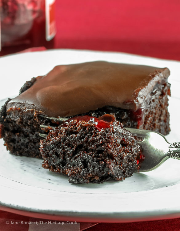 Bite on a fork in front of slice of cake; Chocolate Raspberry Sheet Cake © 2018 Jane Bonacci, The Heritage Cook. All rights reserved.
