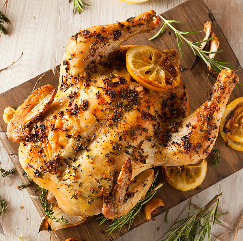 top down look at whole roasted chicken with lemon pieces & fresh herbs; Lemon and Cumin Scented Chicken from The Heritage Cook 2018 Jane Bonacci, The Heritage Cook