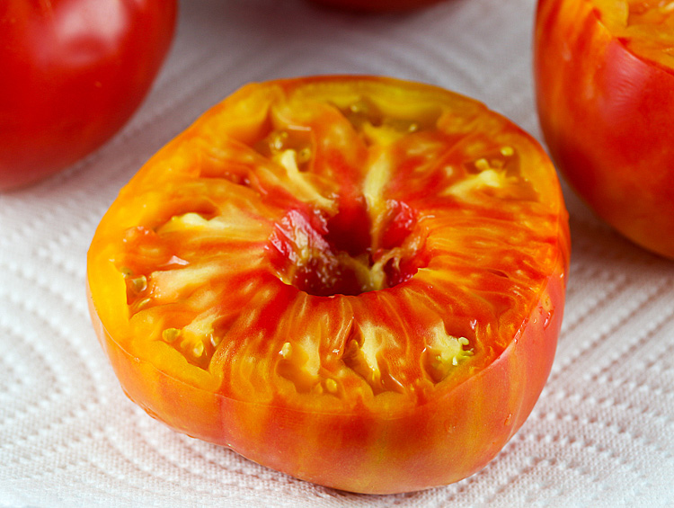 Close up of halved orange heirloom tomato, ready for stuffing