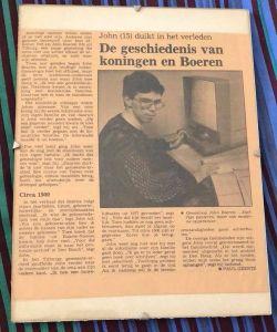 "Newspaper article titled ""De gesheidenisvan koningen en Boeren"" with a subtitle ""John (15) duikt in het verleden"" followed by a photo of John, with dark hair, thick framed glasses and a dark jumper sat at a microfiche reader while looking at the camera."