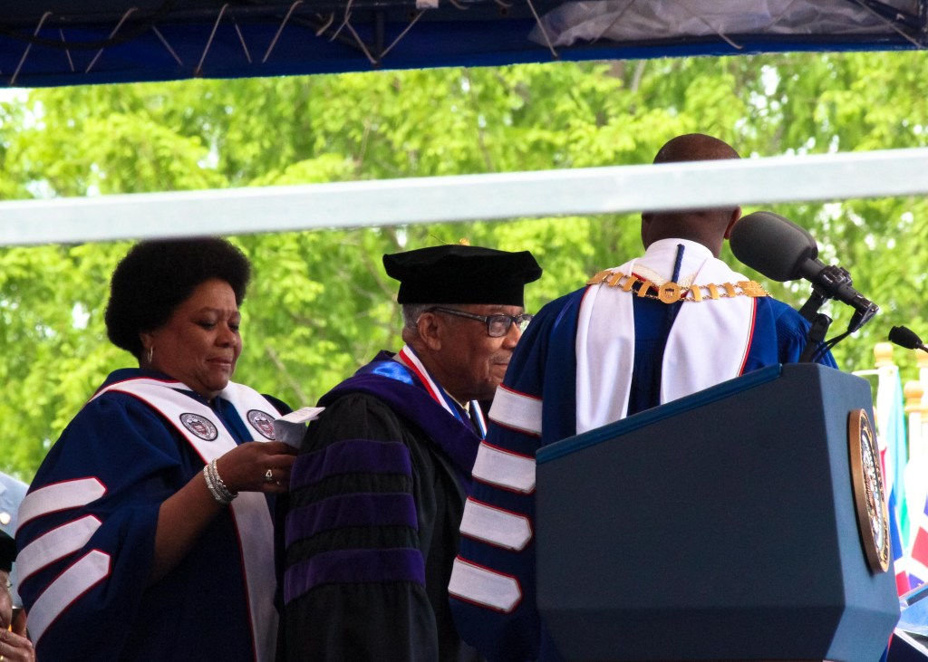 Ambassador Horace G. Dawson, Jr. (middle) receives his honorary degree in doctor of laws by Howard Board of Trustee member Charisse R. Lillie (left) and Howard President Wayne A.I. Frederick (right) May 7th during Howard University's 148th Commencement Convocation. (Photo Credit: Paul Holston/Editor-in-Chief/The Hilltop)