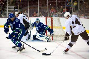 Hershey Bears Center Matt Watkins assists Josh Brittain in scoring on September 27, 2013. (Ann Erling Gofus/The Hockey Writers)
