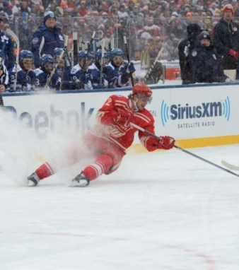 A Red Wing stops hard on his skates creating a snow flurry (Tom Turk/The Hockey Writers)
