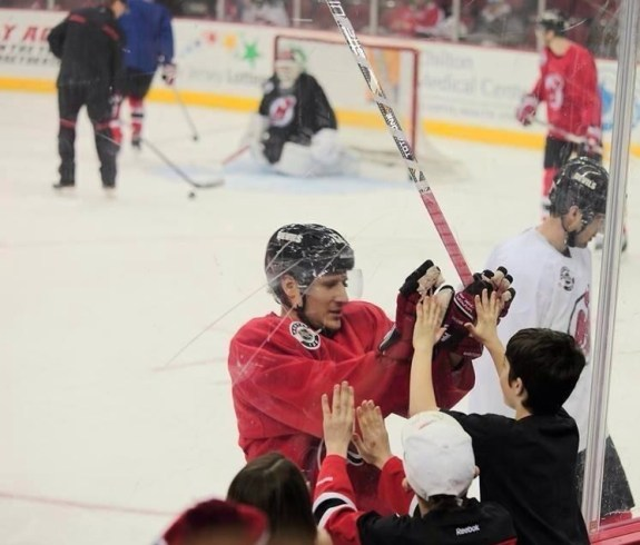 Damien Brunner high-fives a young fan through the glass at an open practice for season ticket holders (Photo by June Glinowiecki Toth)