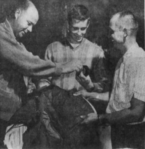 Nashville captain Lloyd Hinchberger, left and goalie Marv Edwards, right, help rookie Ron Hindson with his new uniform.
