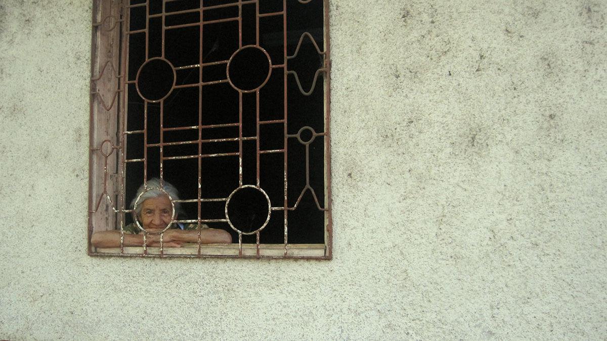 Lady peering out her window in Juayua, El Salvador
