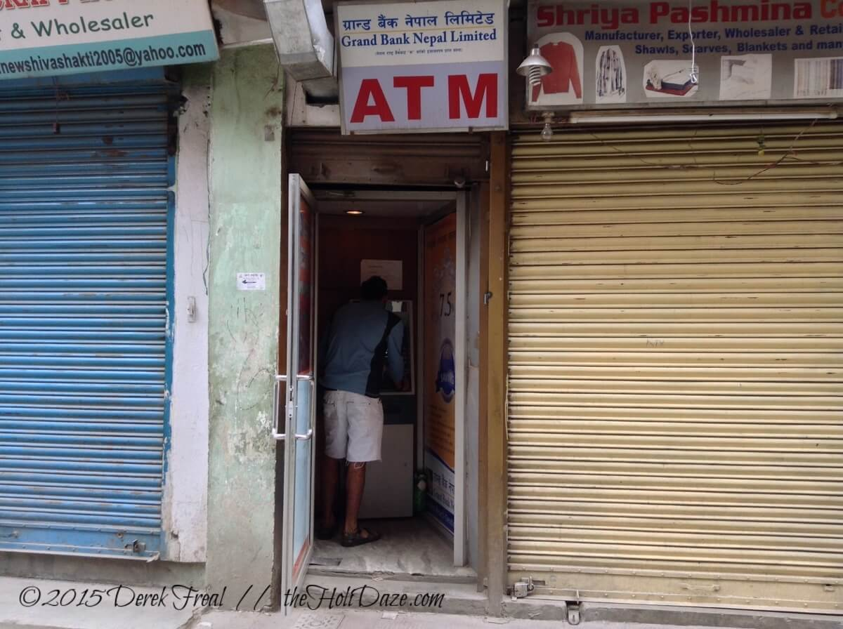A panicked tourist tries fruitlessly to withdrawal money from the ATM minutes after the earthquake.