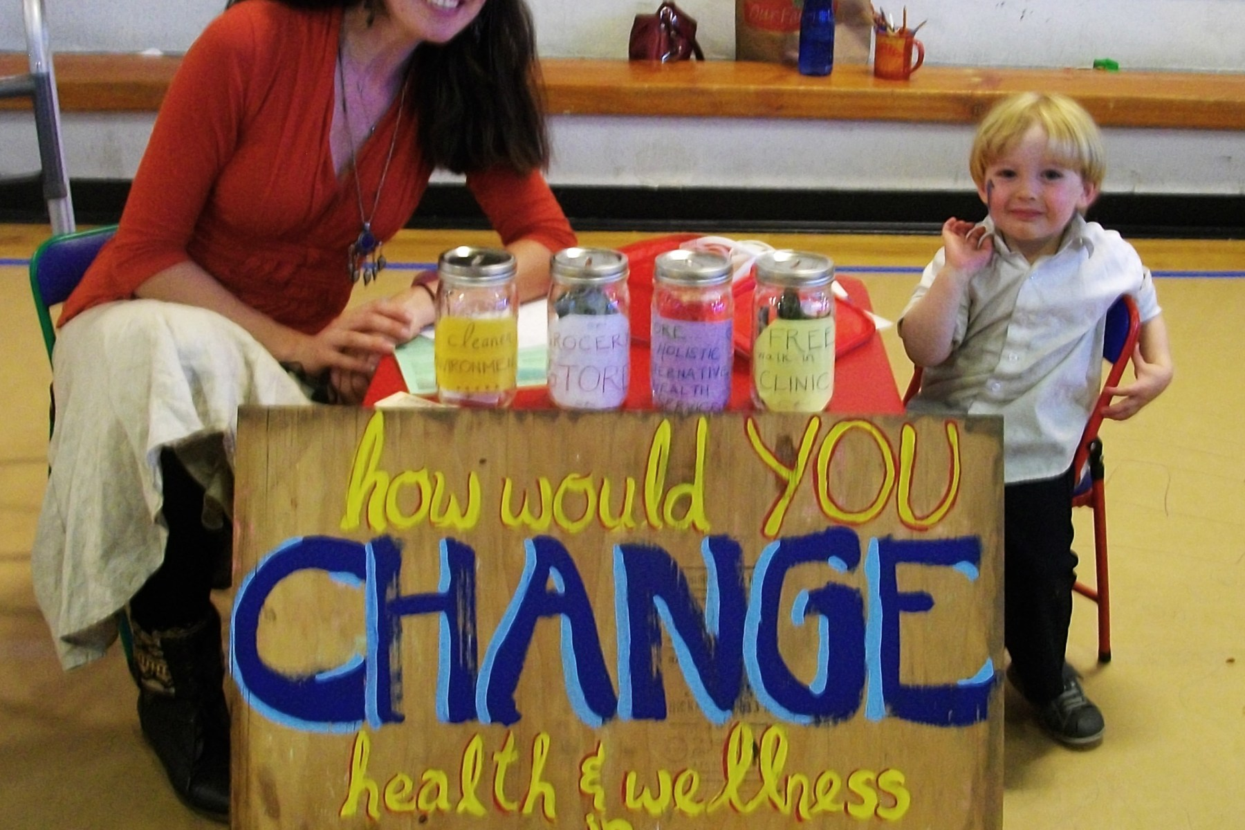 woman and small child with painted sign: How would you change health and wellness in Gilpin County?