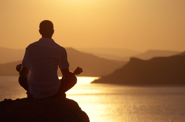 Guy meditating at sunset