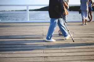 woman walking with a crutch by water