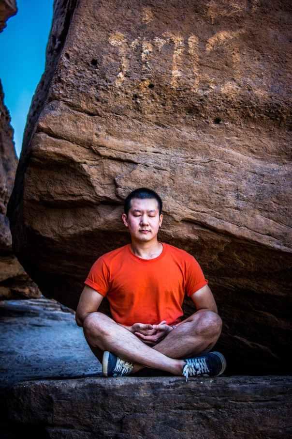 man meditating under rock