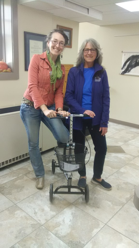 two women standing with a knee walker
