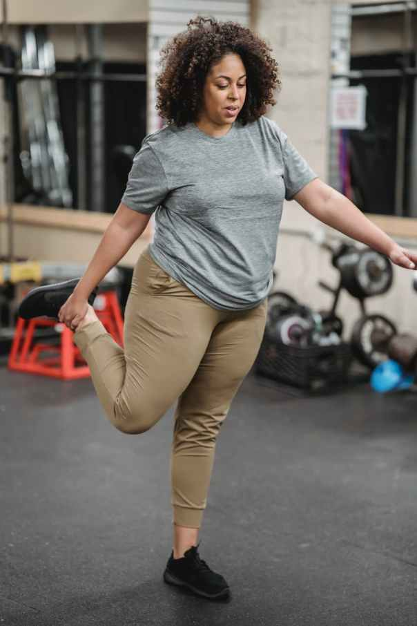 plus size overweight black woman stretching in gym