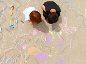 Photograph of children drawing with chalk on the sidewalk. Copyright Some Random Lady