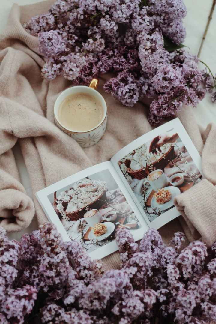 cup of coffee placed on cozy robe near lilac flowers
