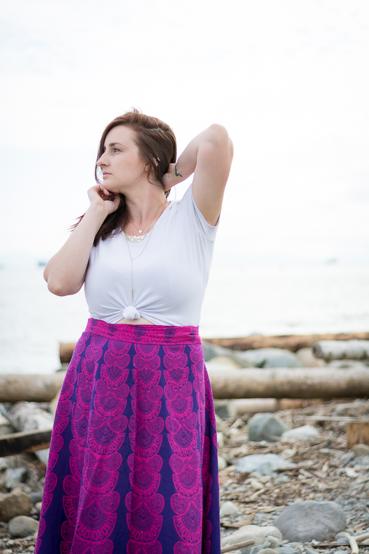 Woman poses on the beach in pink boho maxi skirt